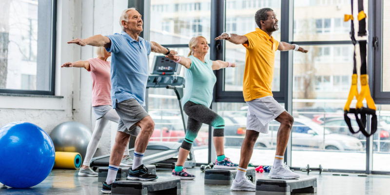 Older adults doing step exercises in the gym